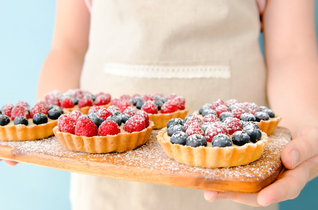 Wooden platter of mixed berry tarts